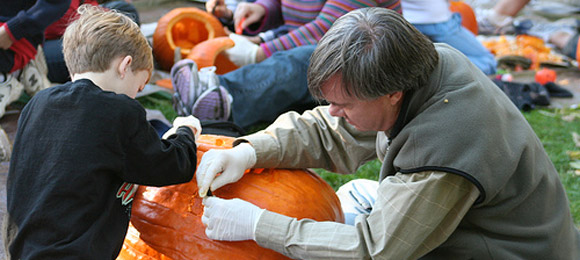 Father and son carving pumpkin
